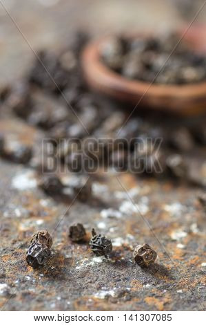 Peppercorns in wooden spoon on texture background