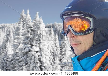 Portrait of skier man in the blue skiing jacket, helmet and glasses against snow forest panorama with copy space