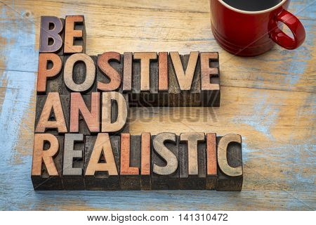 be positive and realistic - motivational text in vintage letterpress wood type printing blocks