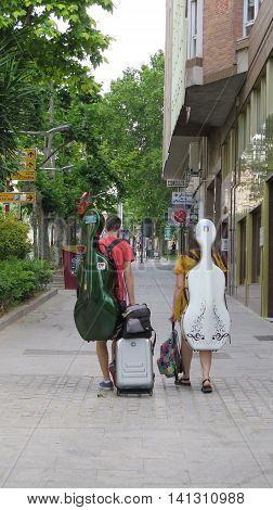 Jaen Spain - June 5 2016: Two musical students walking in leafy street