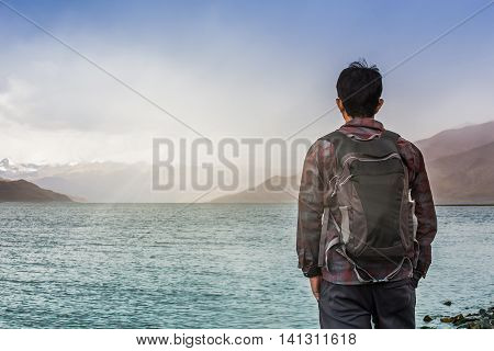 Male tourist looks at Yamdrok lake in Tibet