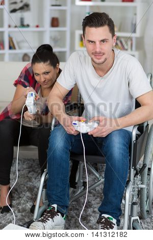young couple playing video games at home boyfriend in wheelchair