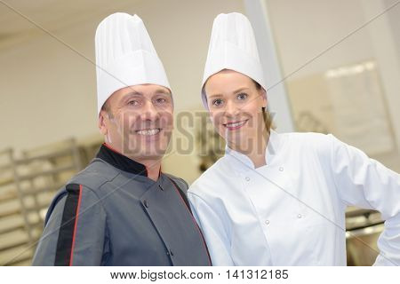 portrait of hospitable chef and his helper at restaurant