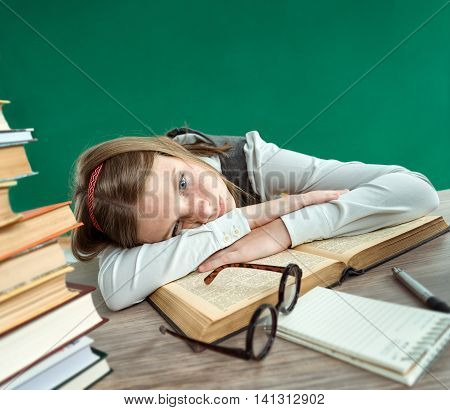 Tired student lies on the books. Photo of schoolgirl creative concept with Back to school theme