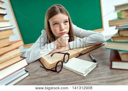 Boredom. Schoolgirl resting her chin on her hands laying on a table with opened book. Creative concept with Back to school theme