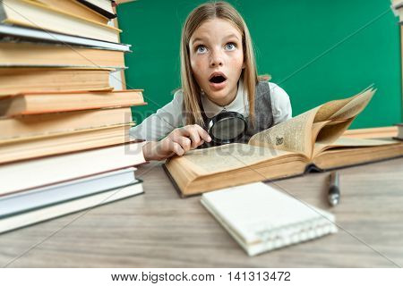Teen interested in reading book with magnifier / photo of teen school girl wearing glasses creative concept with Back to school theme
