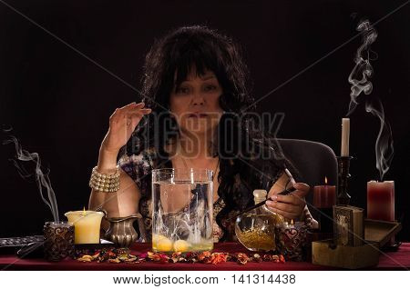 Fortune teller reads a shapes of whites in the water. Black haired old psychic is doing egg divination. She sits at the table surrounded by candles and looks at the camera