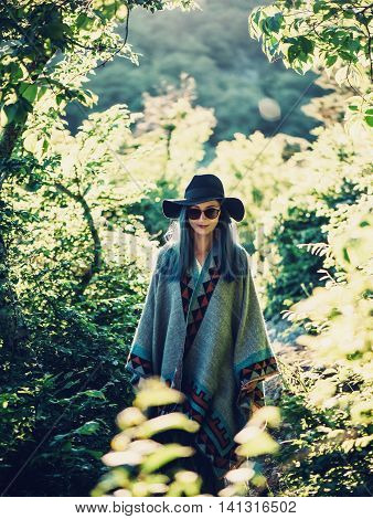 Boho style girl in hat and poncho walking in summer park at sunny day