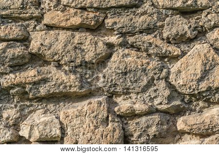 Old wall of large irregular pieces of stone ruins brown background