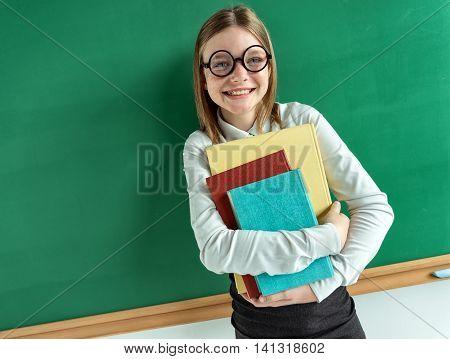 Happy joyful teen girl holding books / photo of teen school girl wearing glasses creative concept with Back to school theme