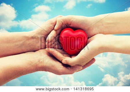 people, age, family, love and health care concept - close up of senior woman and young woman hands holding red heart over blue sky and clouds background