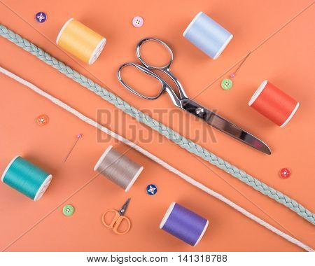 closeup needles thread spool scissors button on orange wooden background.