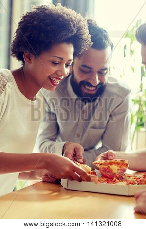 business, food, lunch and people concept - happy business team or friends eating pizza in office