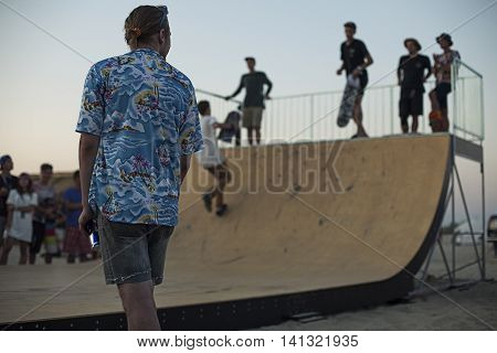 Young skateboarders in skatepark jumping in the halfpipe on beach. Group of friends standing in a row with skateboards in hands. Urban life wallpaper. Youth subculture