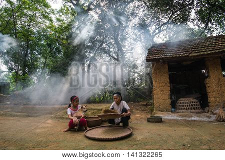 HANOI, VIETNAM, JULY 24, 2016: Countryside old woman do farmer work with her granddaughter in a village in suburb of Hanoi, Vietnam.