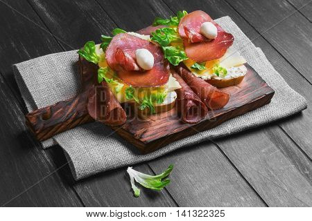 Two sandwiches bruschetta with jerked meat ricotta cheese mozzarella lettuce on a sacking wooden surface
