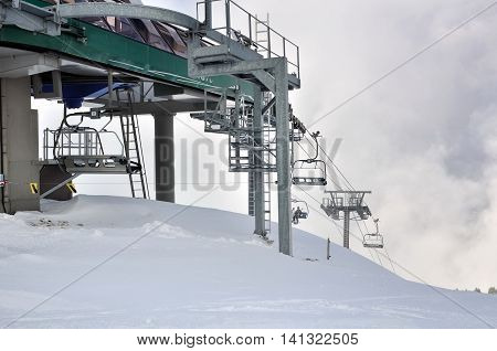 chairlifts in mountain under cloudy sky in winter