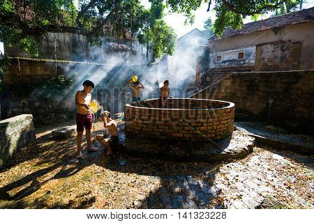 HANOI, VIETNAM, JULY 24, 2016: Countryside children play near the ancient shaft in a village in suburb of Hanoi, Vietnam.