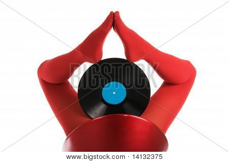 Female feet in red stockings with vinyl record