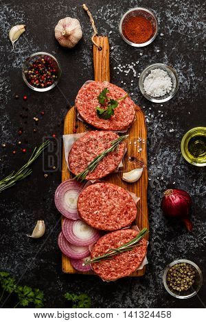 Raw ground beef meat steak cutlets with herbs and spices on dsrk background.