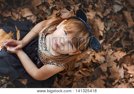 Little girl in the image of cats sitting on dry leaves. An image to celebrate halloween