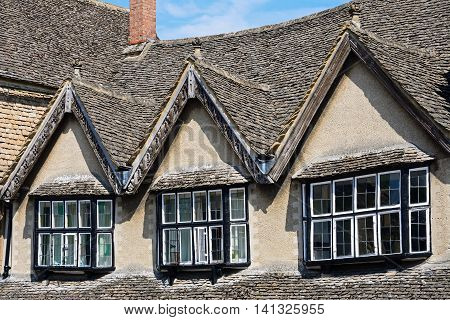Dormer windows above a shop along The Hill shopping street Burford Oxfordshire England UK Western Europe.