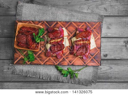 Sandwiches tapas with sun dried tomatoes parsley jerked beef meat plow cheese on cutting board made of wood olive burlap on gray wooden surface in rustic style top view
