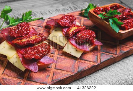 Sandwiches tapas with sun dried tomatoes parsley jerked beef meat plow cheese on cutting board made of wood of olive burlap on a gray wooden surface in a rustic style