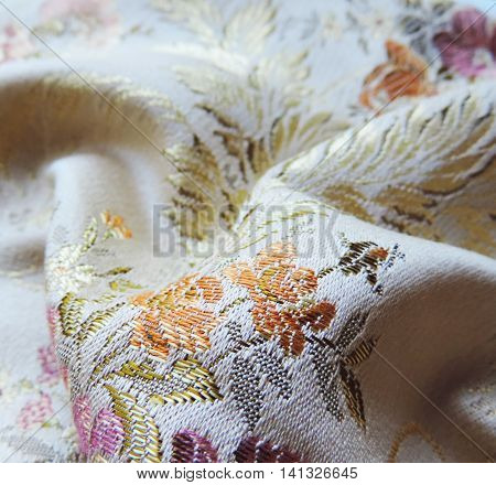 Shiny brocade textile or cloth with floral pattern, close-up shot.