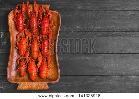 Cancers to beer boiled crawfish beer snacks on wooden tray black dark wooden background top view