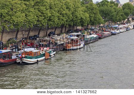 PARIS, FRANCE - MAY 14, 2015: These barges are used by their owners as a floating apartment located in the city center - along the quays of the Seine.