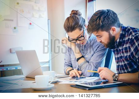 Young businesswoman and businessman working together in office