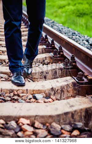 The man in leather shoes walking on the railway sleepers