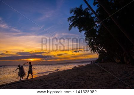 Fishermen At Sunset In Vietnam. Men Go On The Beach With Nets In Hand. The Silhouettes Of The Fisher
