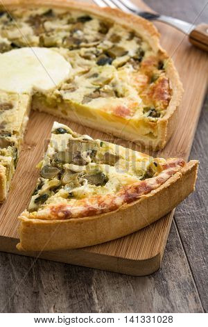 French quiche Lorraine with vegetables on a rustic wooden table