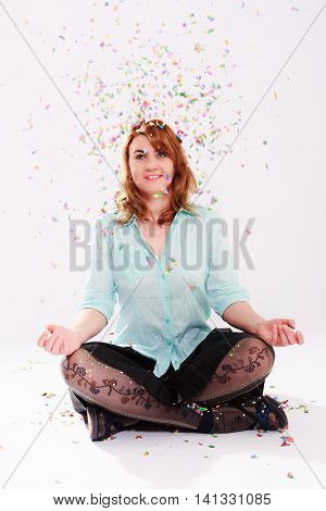 Young woman sitting cross-legged in a shower of confetti.