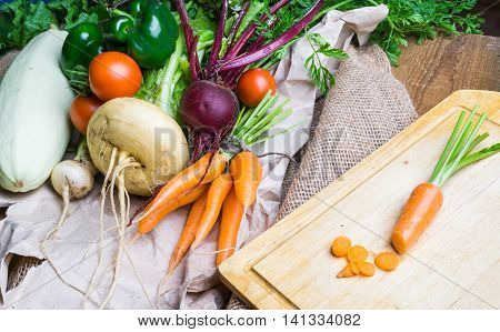 Vegetables on wooden and sackcloth background. Beetroot carrot tomatoes green pepper turnip marrow. Healthy food background