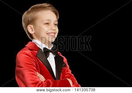 Handsome little boy in a tuxedo on black background