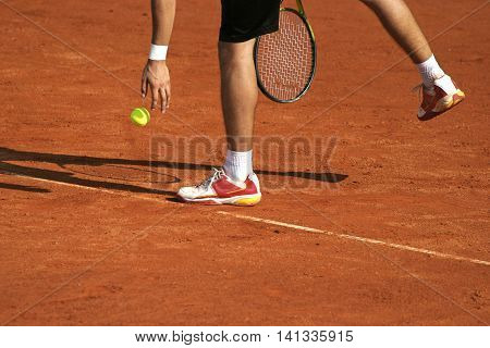 Tennis player preparing for service on clay courts