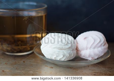 Two pieces of zephyr dessert on a small glass plate and cup of green tea