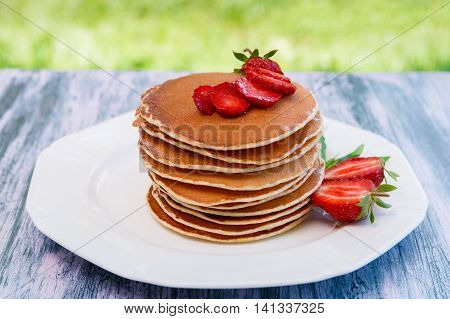 Pancakes with fresh strawberry and mint on white plate on pink wooden background in garden or on nature background. Stack of pancakes on table.
