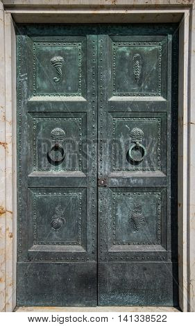 Ancient iron door with carved decorations and circular door knockers.