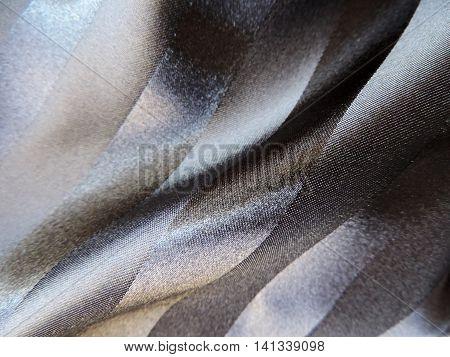 Black satin textile with shiny stripes. Textile background.