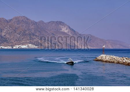 Powerboat the breakwater with a lighthouse in the harbor on the island of Kos