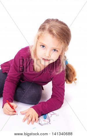 Little cute girl draws pencils sitting on the floor on a white background