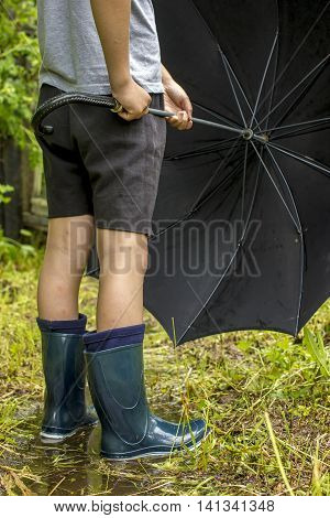 Child in rubber boots stands on a footpath in the puddle after the rain and holds in hands disclosed black an umbrella
