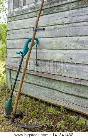electric trimmer and old sharp scythe standing in the garden near the house simply supported on the wall