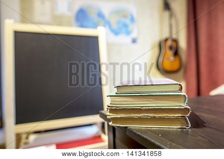 Books lying on a table in a classroom at a private school with a black board card and guitar on the wall
