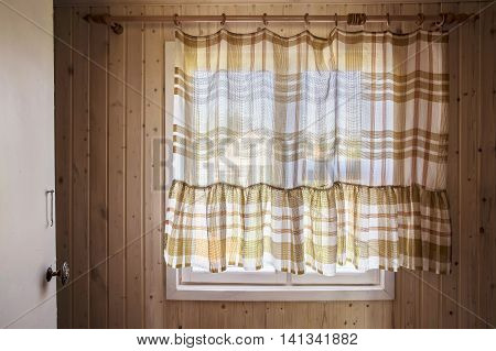 Rustic window from inside the house closed by curtains through which visible nature the neighboring houses and the sky.