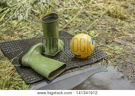 green baby boots filled with water under the rain on a black the rubber mat lies next the yellow ball on a background green grass